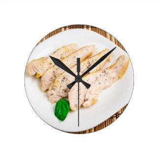 Gebackene Hühnerbrust geschnitten auf einer weißen Runde Wanduhr