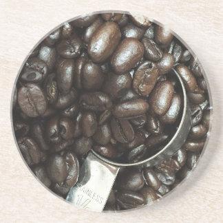 Gebratene Kaffeebohnen mit silberner Getränkeuntersetzer