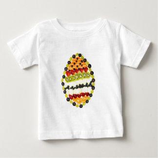 Geformte Fruchttorte des Eies mit verschiedenen Baby T-shirt