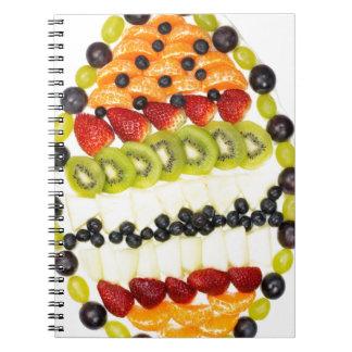 Geformte Fruchttorte des Eies mit verschiedenen Spiral Notizblock
