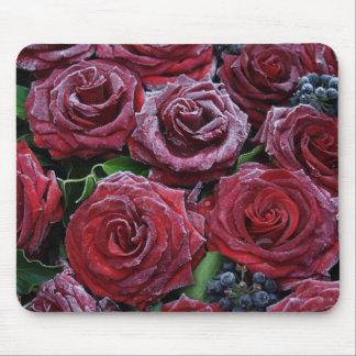 Gefrorene dunkelrote Rosen auf einem Grab Mauspads
