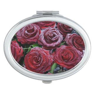Gefrorene dunkelrote Rosen auf einem Grab Schminkspiegel