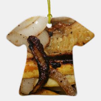 Gegrillte Zwiebelscheiben und Stücke des gelben Keramik T-Shirt-Ornament