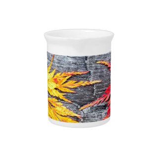 Gelb und Rotahornblatt auf Schwarzem brannten Holz Krug