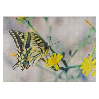 Gelbe Blumen und schöner Schmetterling Schneidebrett