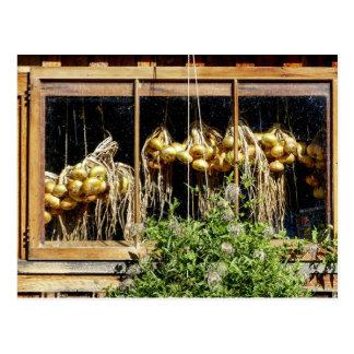 Gelbe Zwiebeln, die durch ein Fenster hängen Postkarte