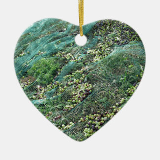 Gerade ausgewählte Oliven auf dem Netz während der Keramik Herz-Ornament
