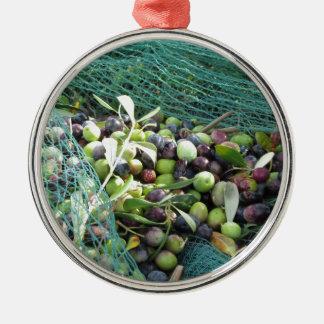 Gerade ausgewählte Oliven auf dem Netz während der Silbernes Ornament