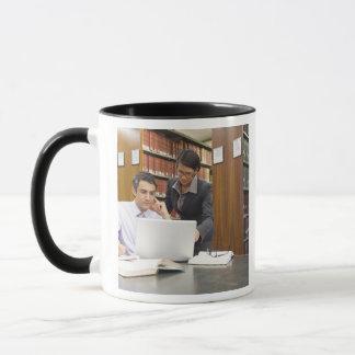 Geschäftsleute, die Forschung in der Bibliothek Tasse