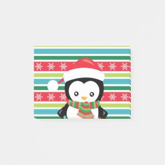 Geschenk-Pinguin auf gestreiftem Post-it Klebezettel