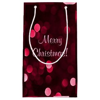 Glänzende rote Weihnachtslichter Bokeh frohe Kleine Geschenktüte