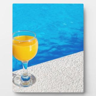 Glas mit Orangensaft auf Rand des Swimmingpools Fotoplatte