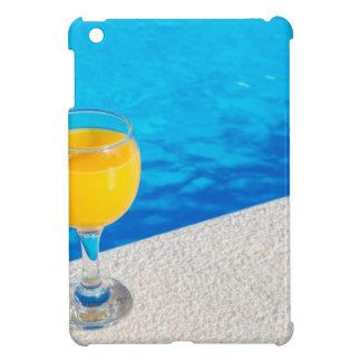 Glas mit Orangensaft auf Rand des Swimmingpools iPad Mini Hülle