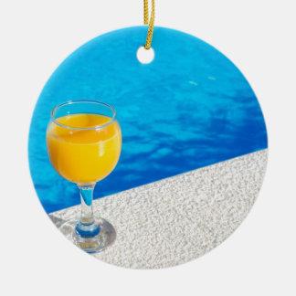Glas mit Orangensaft auf Rand des Swimmingpools Keramik Ornament