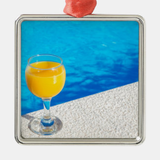 Glas mit Orangensaft auf Rand des Swimmingpools Silbernes Ornament