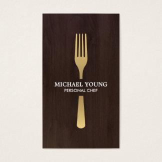 GOLDENE GABEL auf dunklem hölzernem Koch, Catering Visitenkarte