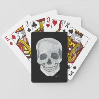 Grauer Schädel auf schwarzen Spielkarten