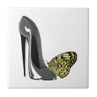 Grauer Stilett-Schuh und gelbe Keramikfliese