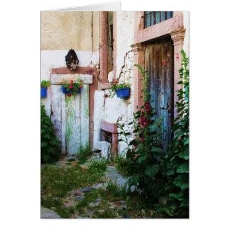 Griechische blaue Tür im Blumen-Garten in Karte