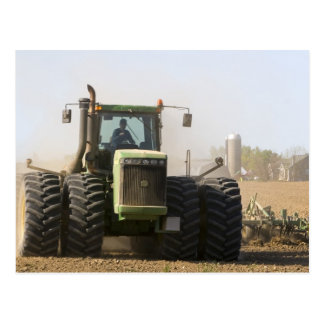 Großer Traktor, der Frühlingsboden auf a Postkarte