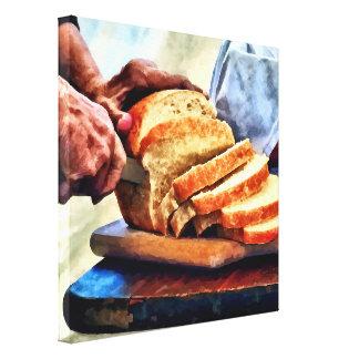 Großmutter, die Brot schneidet Leinwanddruck