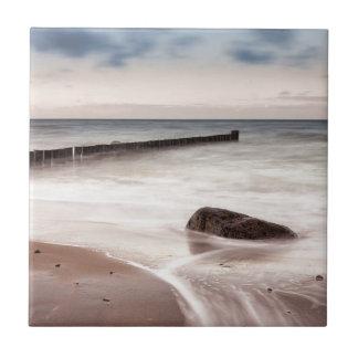Groynes und Steine auf der Ostsee fahren die Küste Fliese