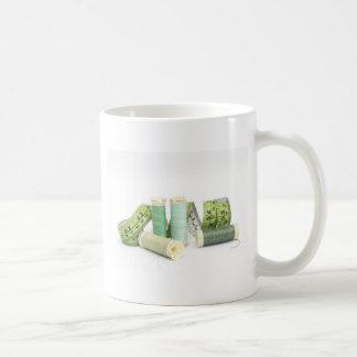 Grüne nähende Ausrüstung und Faden Kaffeetasse