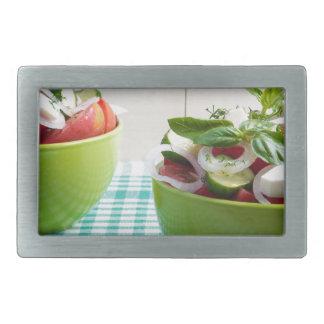 Grüne Schüssel zwei mit vegetarischem Gemüsesalat Rechteckige Gürtelschnallen