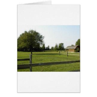 Grüner Rasen mit hölzernem Zaun und Bäumen Karte