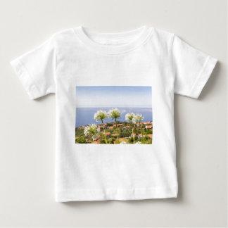 Gruppe des weißen Agapanthus nahe Dorf und Meer Baby T-shirt