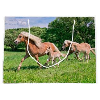 Haflinger Pferde mit niedlichen Fohlen lassen Große Geschenktüte
