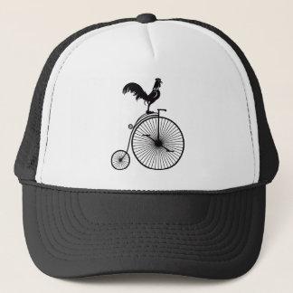 Hahn, der auf Vintagem Penny-Farthing-Fahrrad Truckerkappe