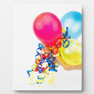Hand, die bunte Ballone mit Bändern gibt Fotoplatte