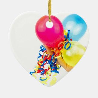 Hand, die bunte Ballone mit Bändern gibt Keramik Herz-Ornament