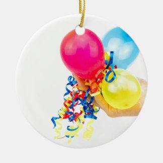 Hand, die bunte Ballone mit Bändern gibt Keramik Ornament