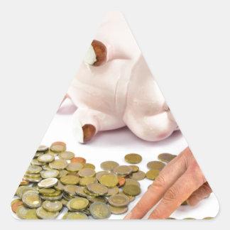 Hand, die Euromünzen von der piggy Bank zählt Dreieckiger Aufkleber