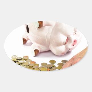 Hand, die Euromünzen von der piggy Bank zählt Ovaler Aufkleber
