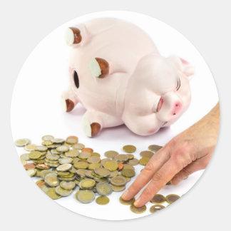 Hand, die Euromünzen von der piggy Bank zählt Runder Aufkleber