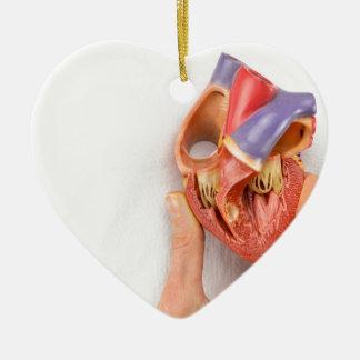 Hand, die Herzmodell vor Kasten hält Keramik Ornament