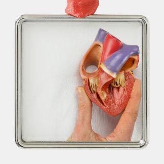 Hand, die Herzmodell vor Kasten hält Quadratisches Silberfarbenes Ornament