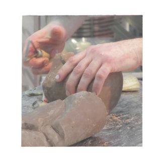 Hände schnitten eine Skulptur von einer Schokolade Notizblock