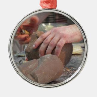 Hände schnitten eine Skulptur von einer Schokolade Silbernes Ornament