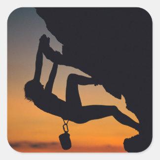 Hängender Kletterer am Sonnenaufgang Quadrat-Aufkleber