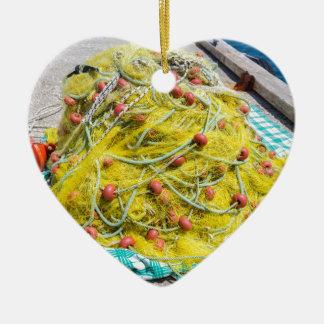 Haufen des gelben Fishnet auf dem Boden in Meer Keramik Herz-Ornament