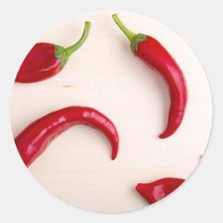 Heiße Chili-Paprikaschoten auf einem hellen Runder Aufkleber