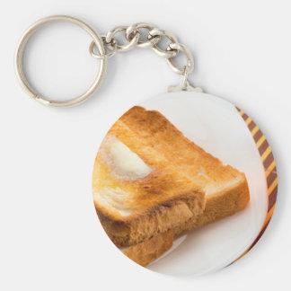 Heißer Toast mit Butter auf einer weißen Platte Schlüsselanhänger