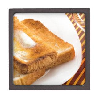 Heißer Toast mit Butter auf einer weißen Platte Schmuckkiste