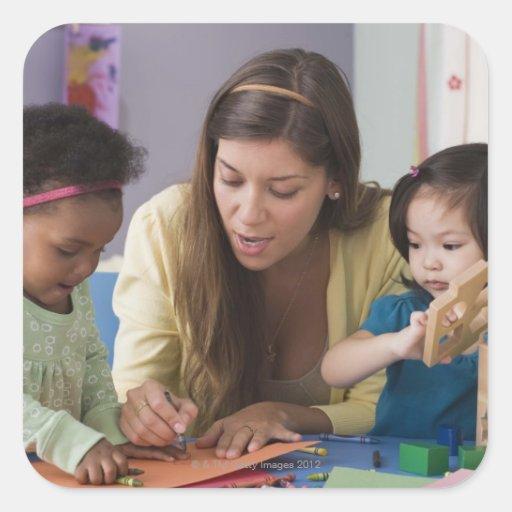 Helfende Kleinkindfarbe des Lehrers am Kindertages Quadratsticker