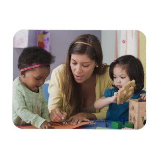 Helfende Kleinkindfarbe des Lehrers am Kindertages Eckiger Magnet