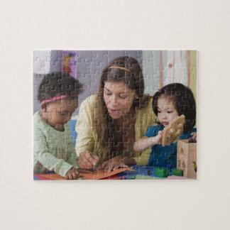 Helfende Kleinkindfarbe des Lehrers am Kindertages Jigsaw Puzzle